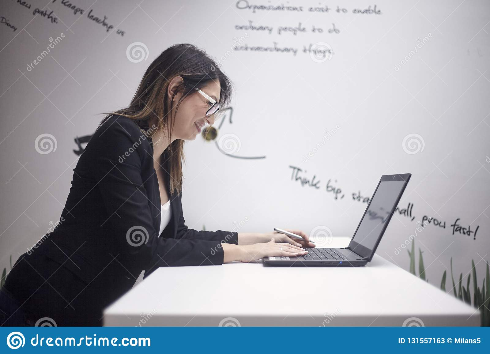 One young smiling woman 30 39 years old side view upper body shot working on laptop wall with creative quotes behind