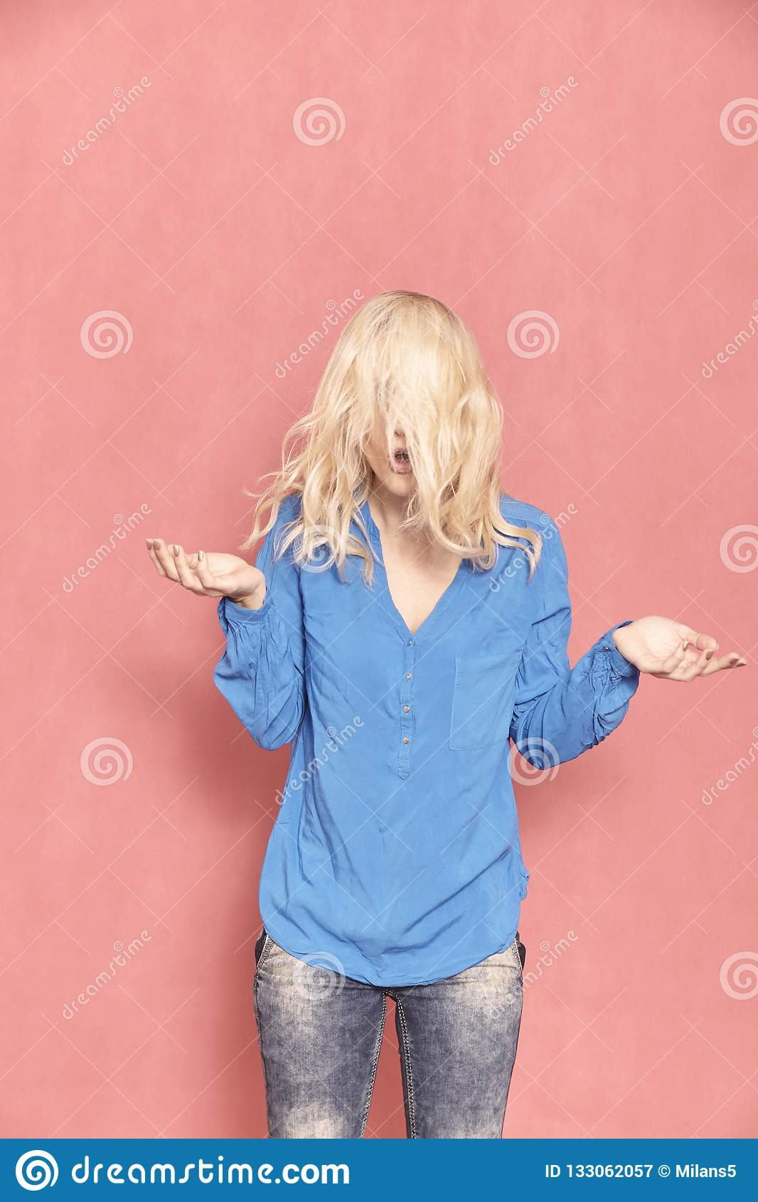One young woman, 20-29 years old, messy chaotic long blond hair, almost hilarious since her face can `t be seen, arm`s raised in d