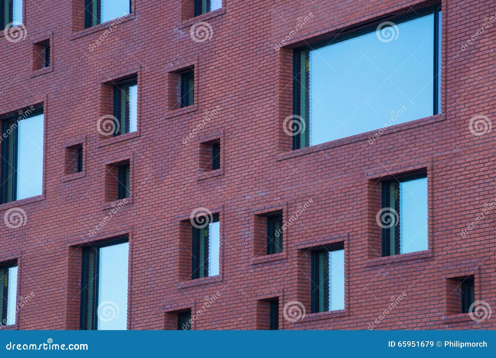 Oneven met maat vensters op bakstenen muur van de moderne for Moderne bouw
