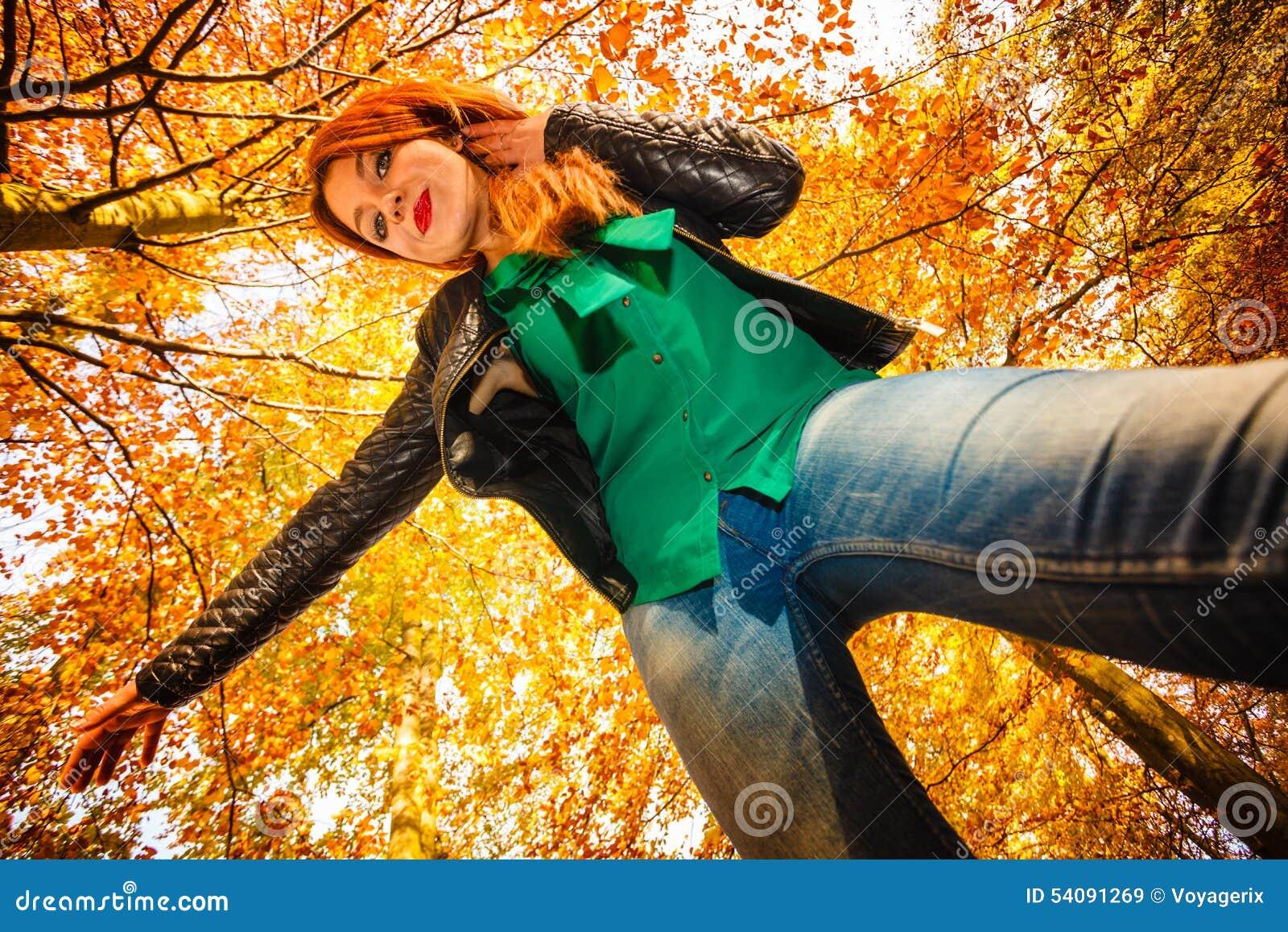 Ongebruikelijke hoek van jonge vrouw in de herfstpark
