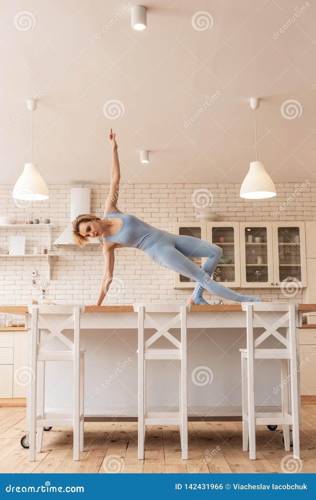 Ongebruikelijke magere jonge uitvoerder die op keukenlijst dansen