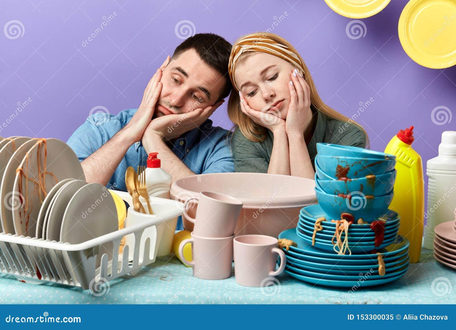 Ongelukkig vermoeid slaperig paar die op het lijsthoogtepunt leunen van vuile platen en koppen