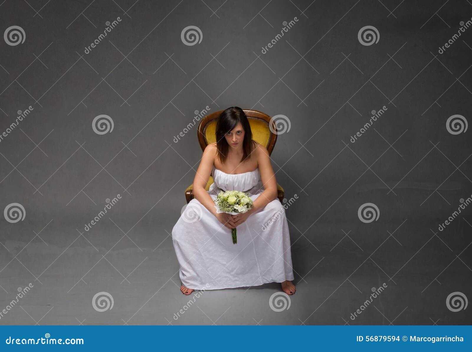 Ongelukkige bruidzitting met boeket op hand