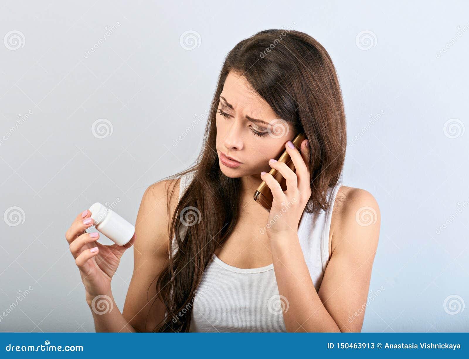 Ongelukkige verwarde jonge vrouwenholding en het kijken op de tabletfles in de hand en uitnodigend mobiele telefoon om de arts te