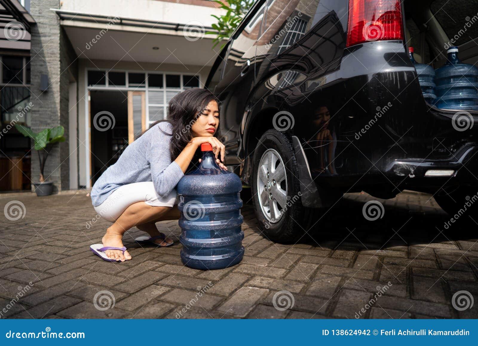 Ongelukkige vrouw die een gallon water dragen