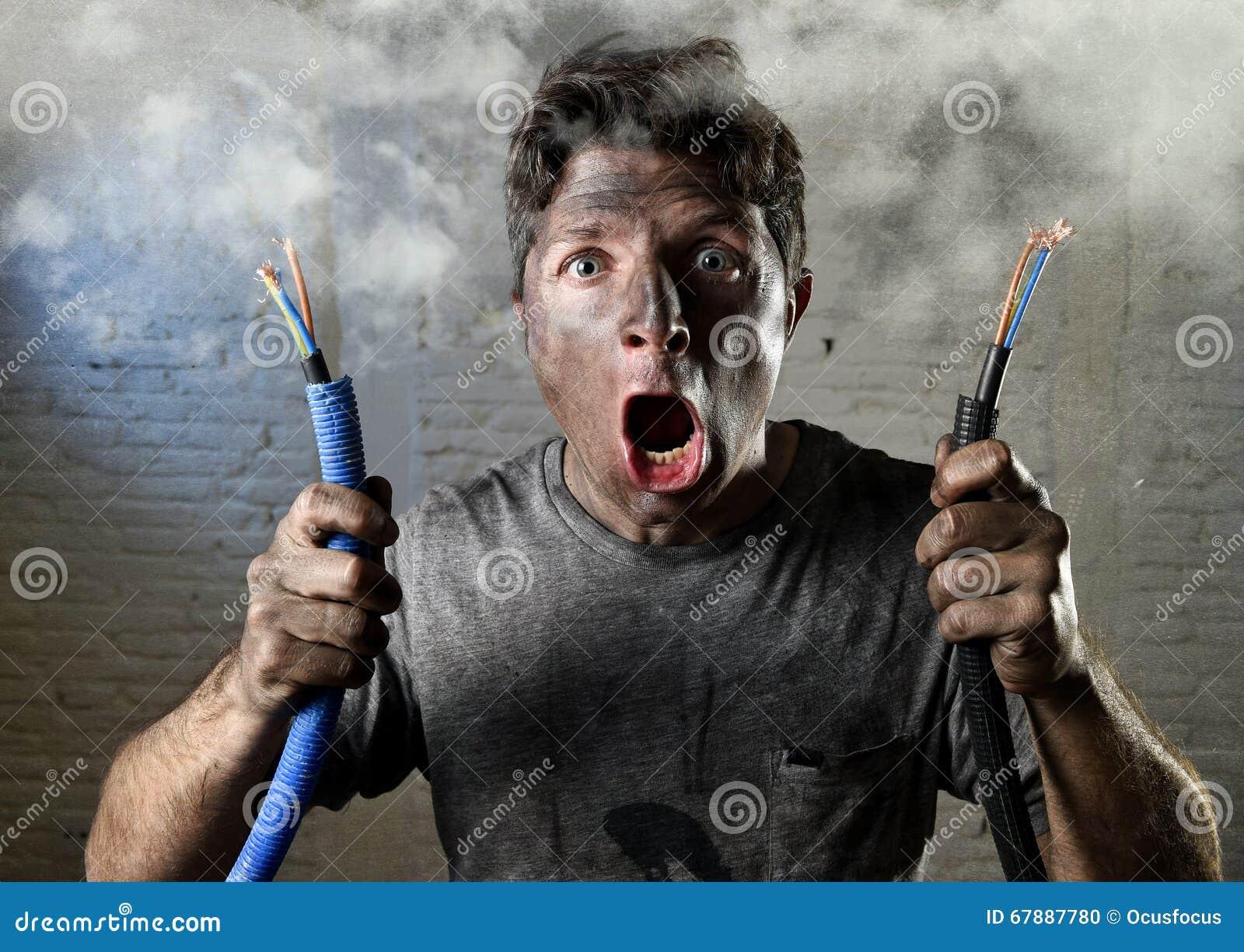 Ongeoefende mens die zich bij elektrokabel aansluiten die aan elektroongeval met vuil gebrand gezicht in grappige schokuitdrukkin