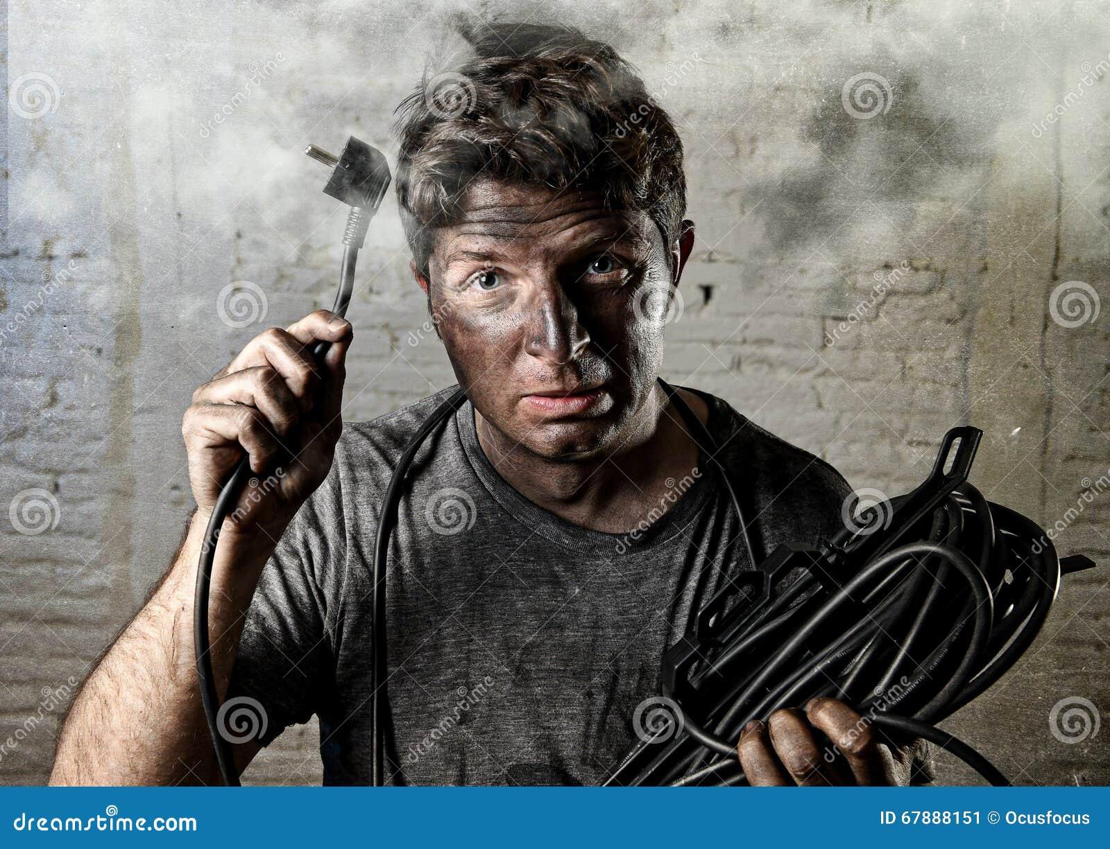 Ongeoefende mensenkabel die aan elektroongeval met vuil gebrand gezicht in grappige schokuitdrukking lijden