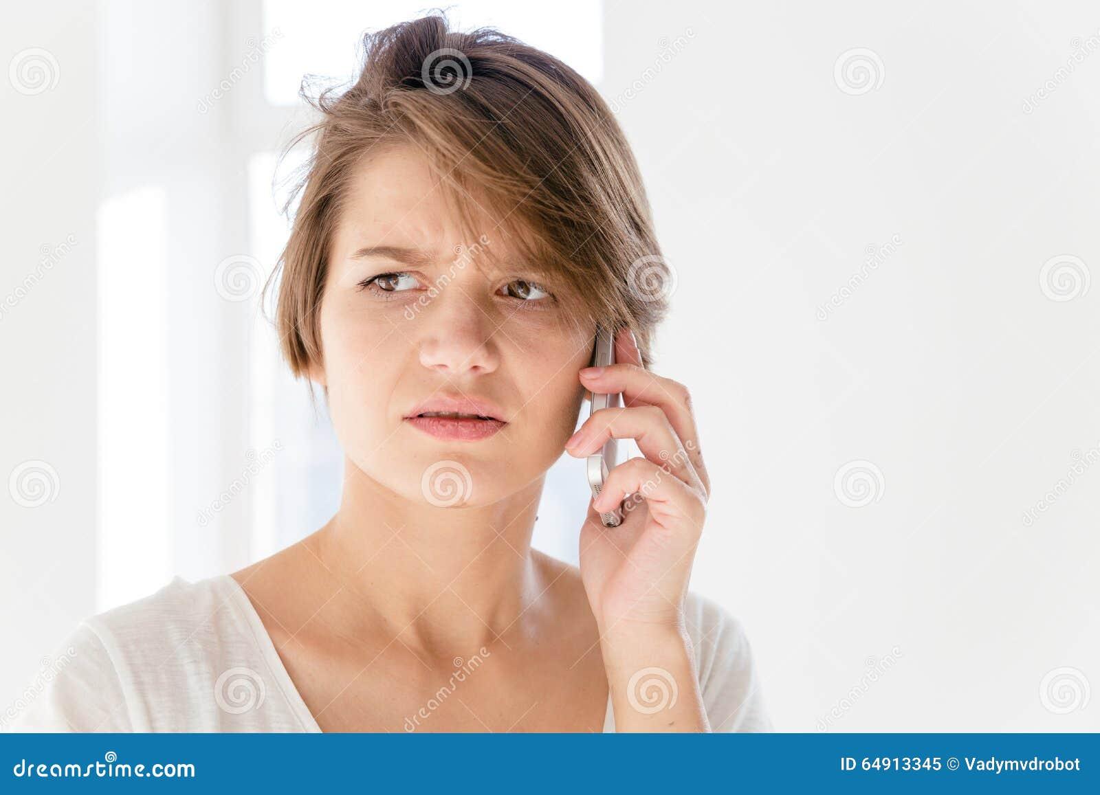 Ongerust gemaakte gestoorde jonge vrouw die op mobiele telefoon spreken
