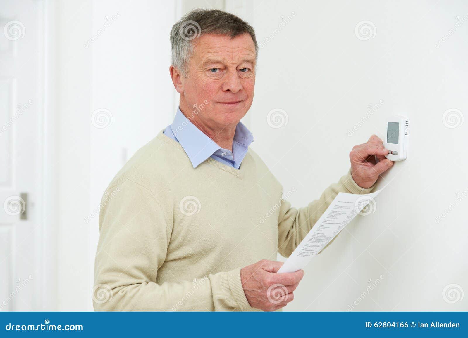 Ongerust gemaakte Hogere Mens met Bill Turning Down Heating Thermostat