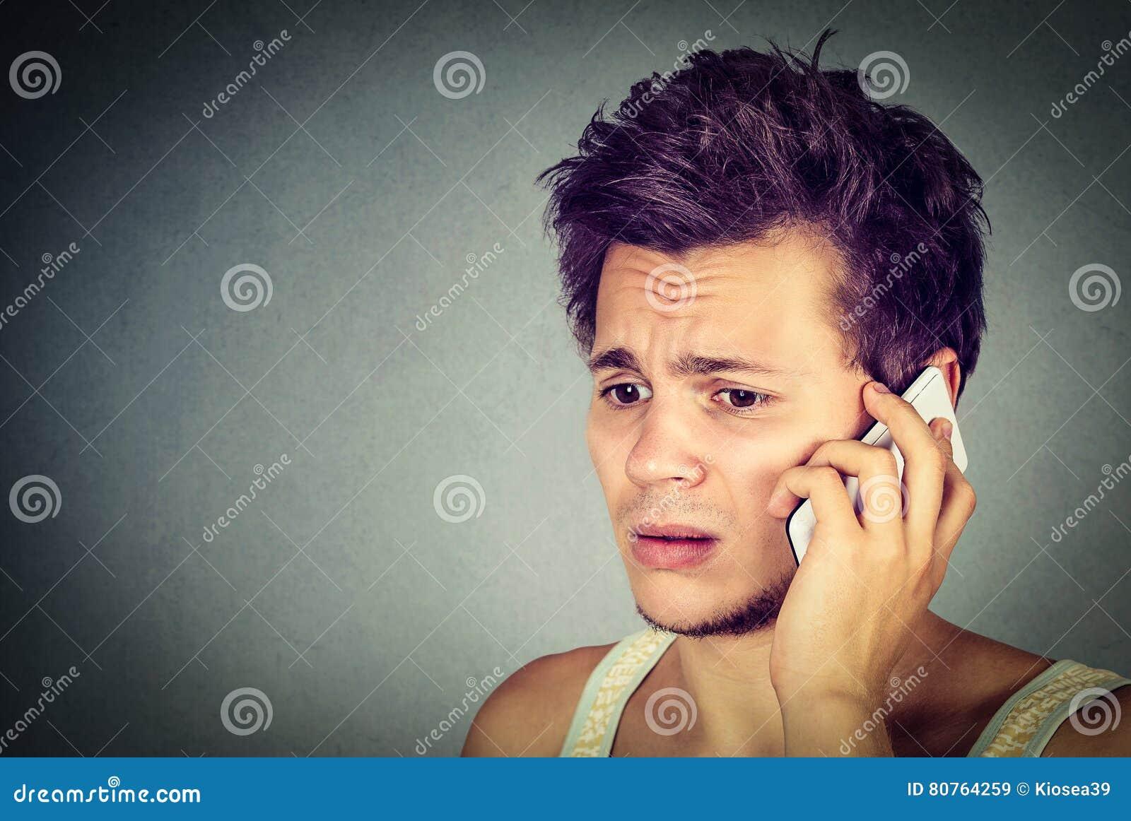 Ongerust gemaakte jonge mens die op telefoon aan iemand spreken die verstoord kijken