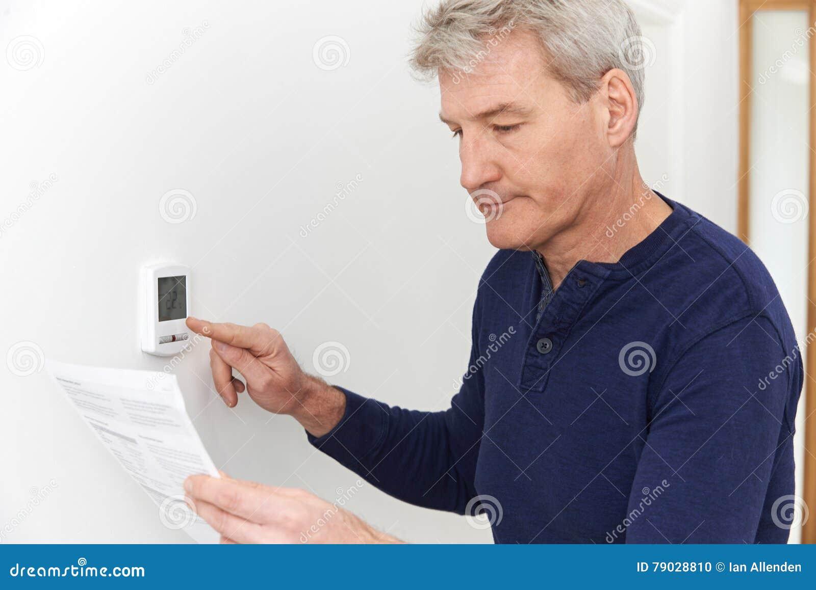 Ongerust gemaakte Rijpe Mens met Bill Turning Down Heating Thermostat