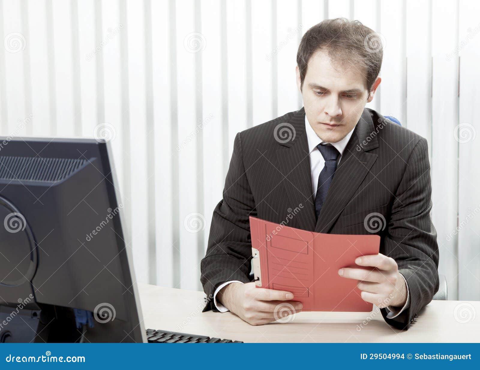 Ongerust gemaakte zakenman die een document lezen bij zijn bureau