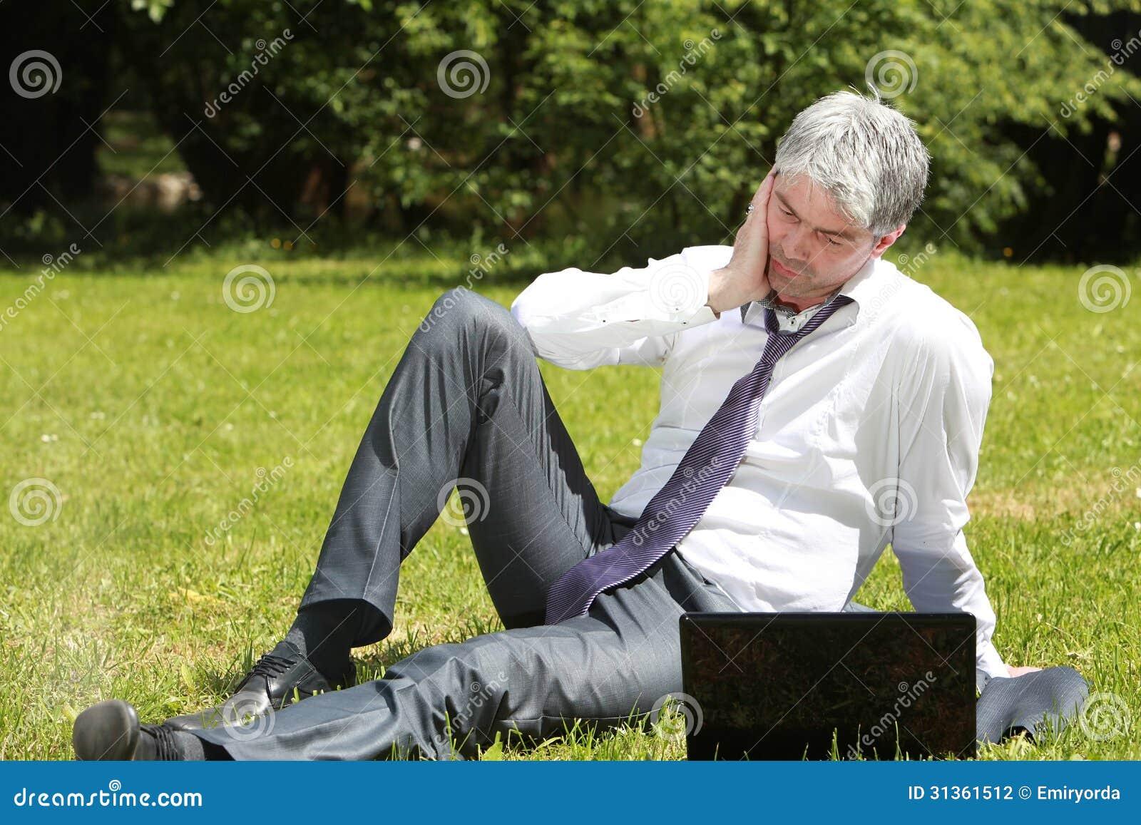 Ongerust gemaakte zakenman die laptop op een weide met behulp van