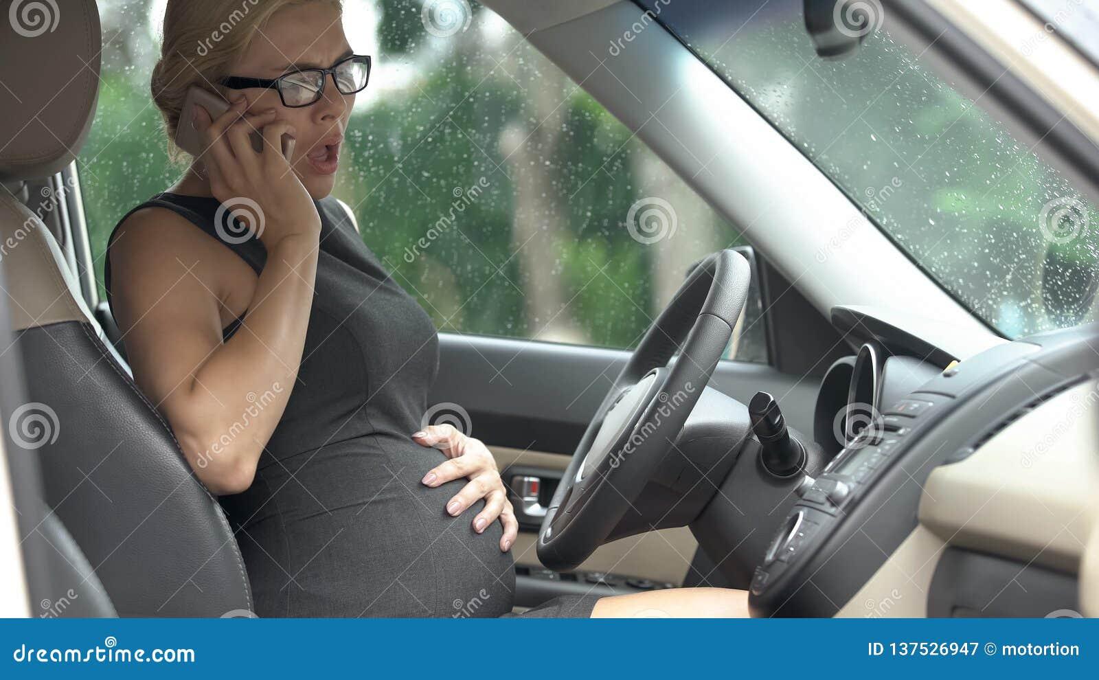 Ongerust gemaakte zwangere vrouwelijke roepende ziekenwagen, die in auto, vroege baring zitten