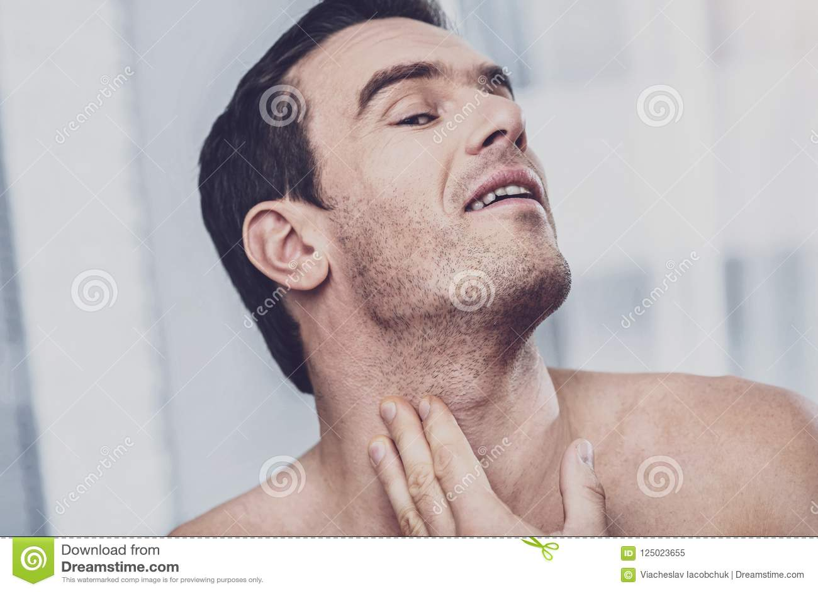 Ongeschoren mens die varkenshaar van zijn gezicht bekijken