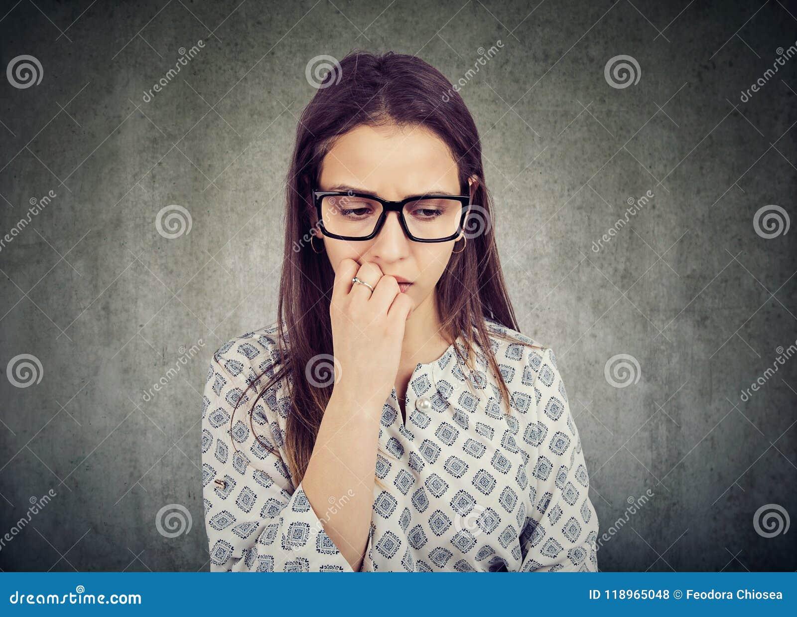 Ongles acérés de femme nerveuse et regard vers le bas