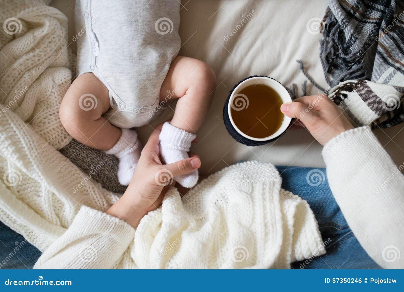 Onherkenbare moeder met het pasgeboren babyzoon liggen op bed