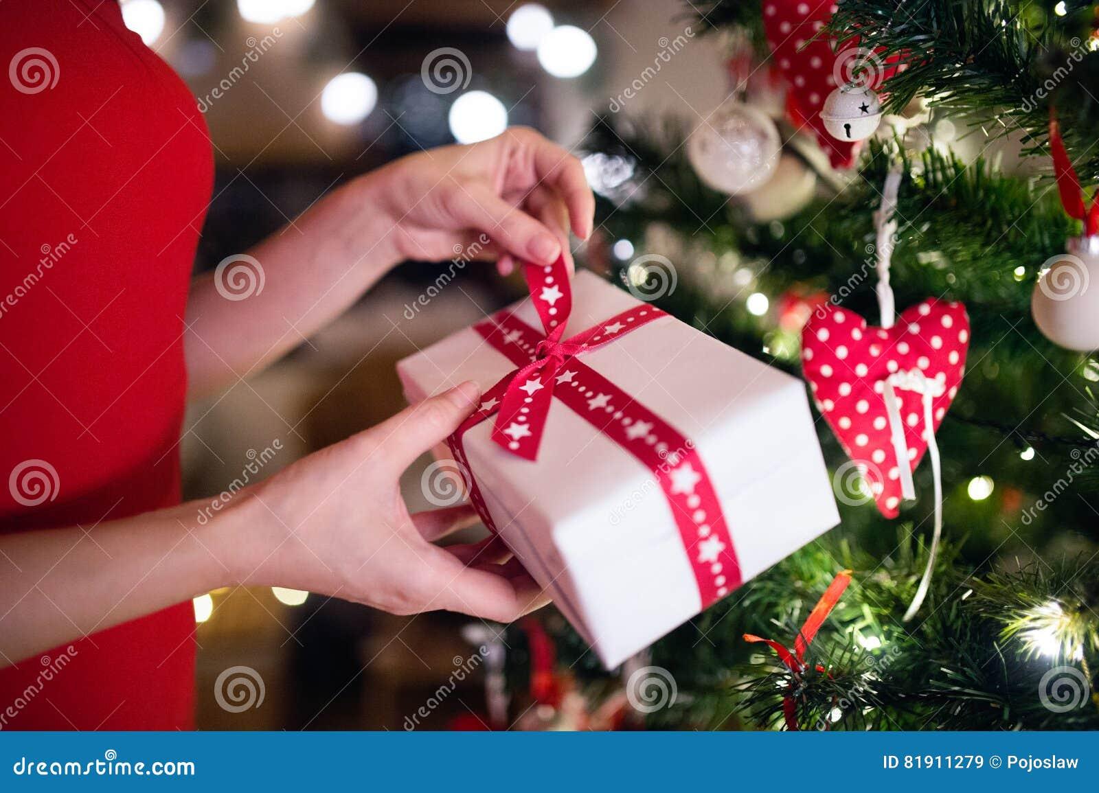 Onherkenbare vrouw voor Kerstboom met heden