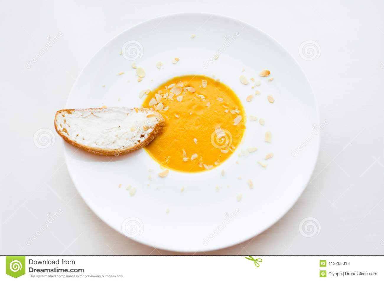 Onion cream soup with toast. Vegetable cream soup with pumpkin in a white bowl and a slice of bread with cheese. Healthy food. Hea