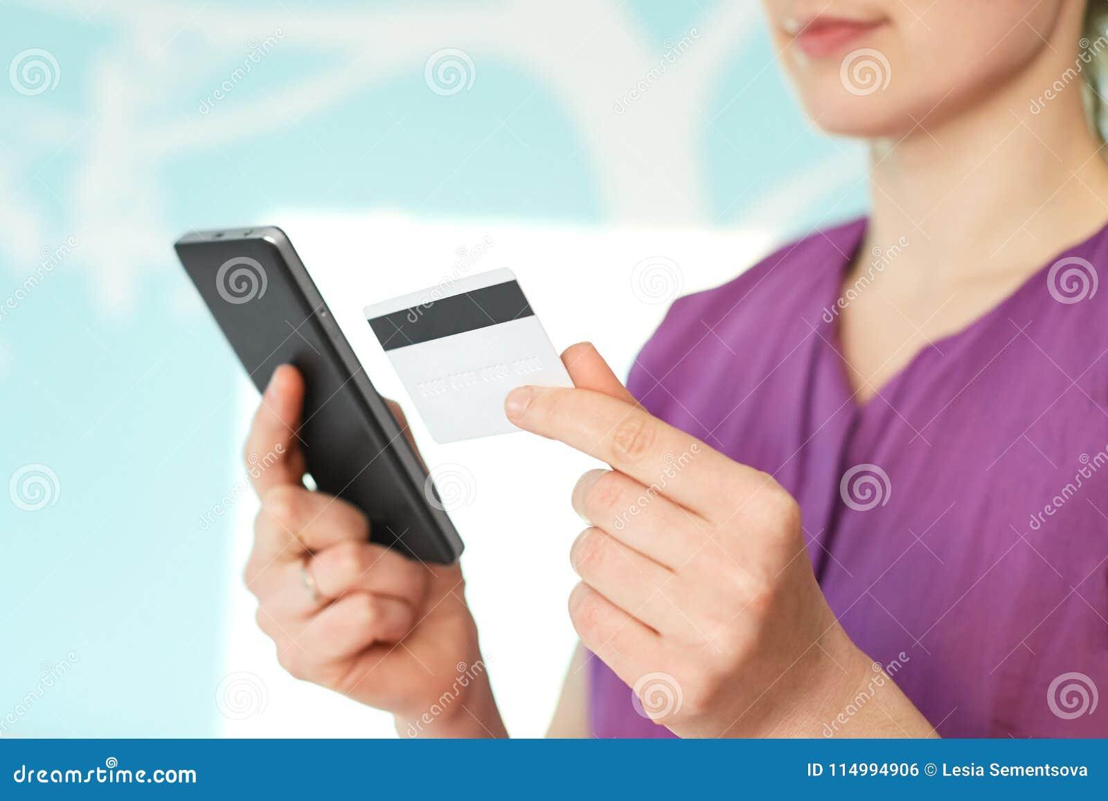 Online het winkelen concept Sluit van onherkenbaar vrouwelijk model toont moderne mobiele telefoon en creditcard, surfes Internet