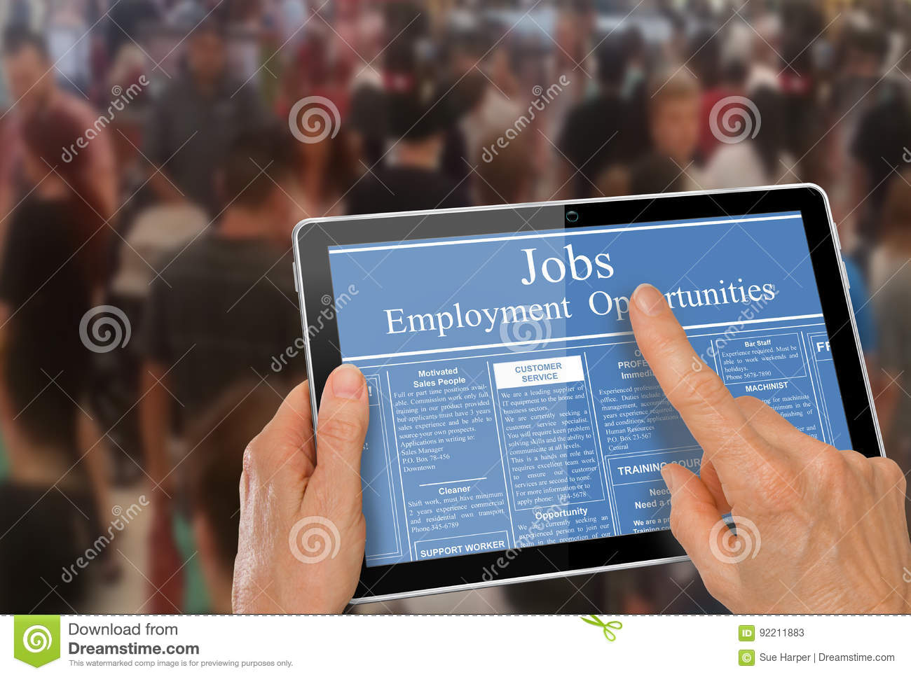 Online job hunting Hands with computer tablet reading employment ads infront of crowd of people