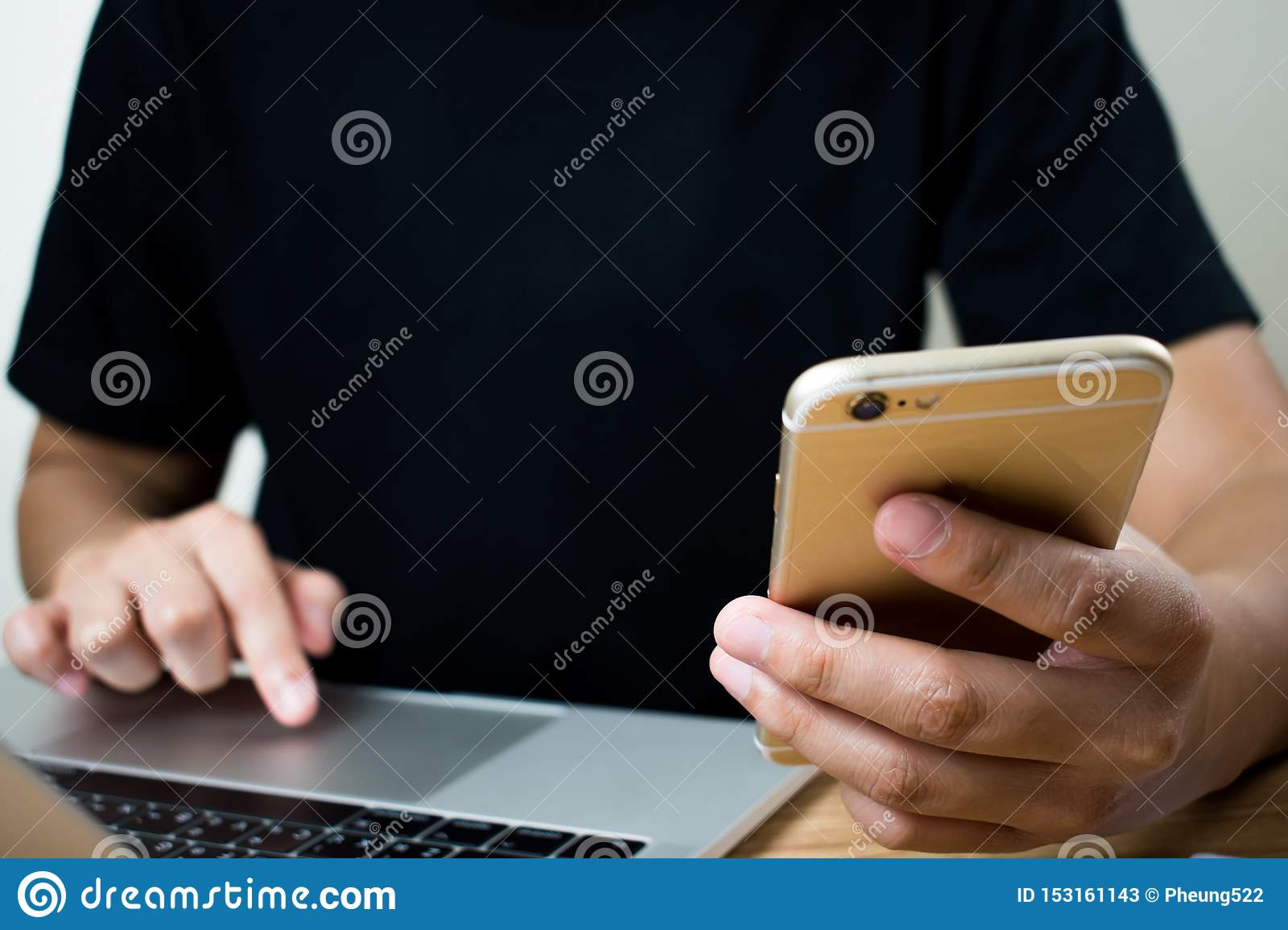 Online shopping concept. The hands of people are using mobile phones and laptop computers to compare something on the table