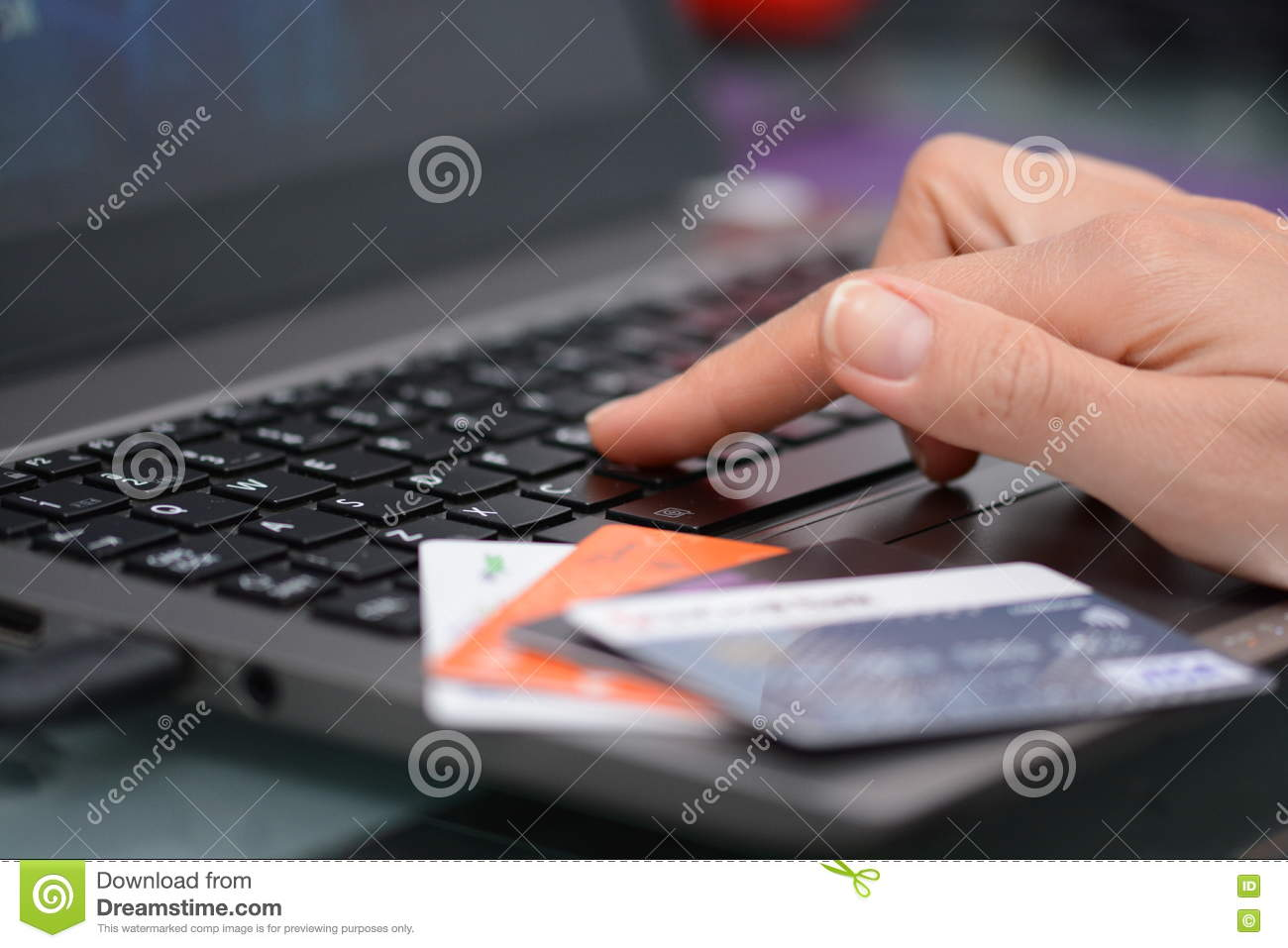 7e49bc0802d Close-up of Woman hand using a laptop and different colored credit cards  for online shopping or for internet banking