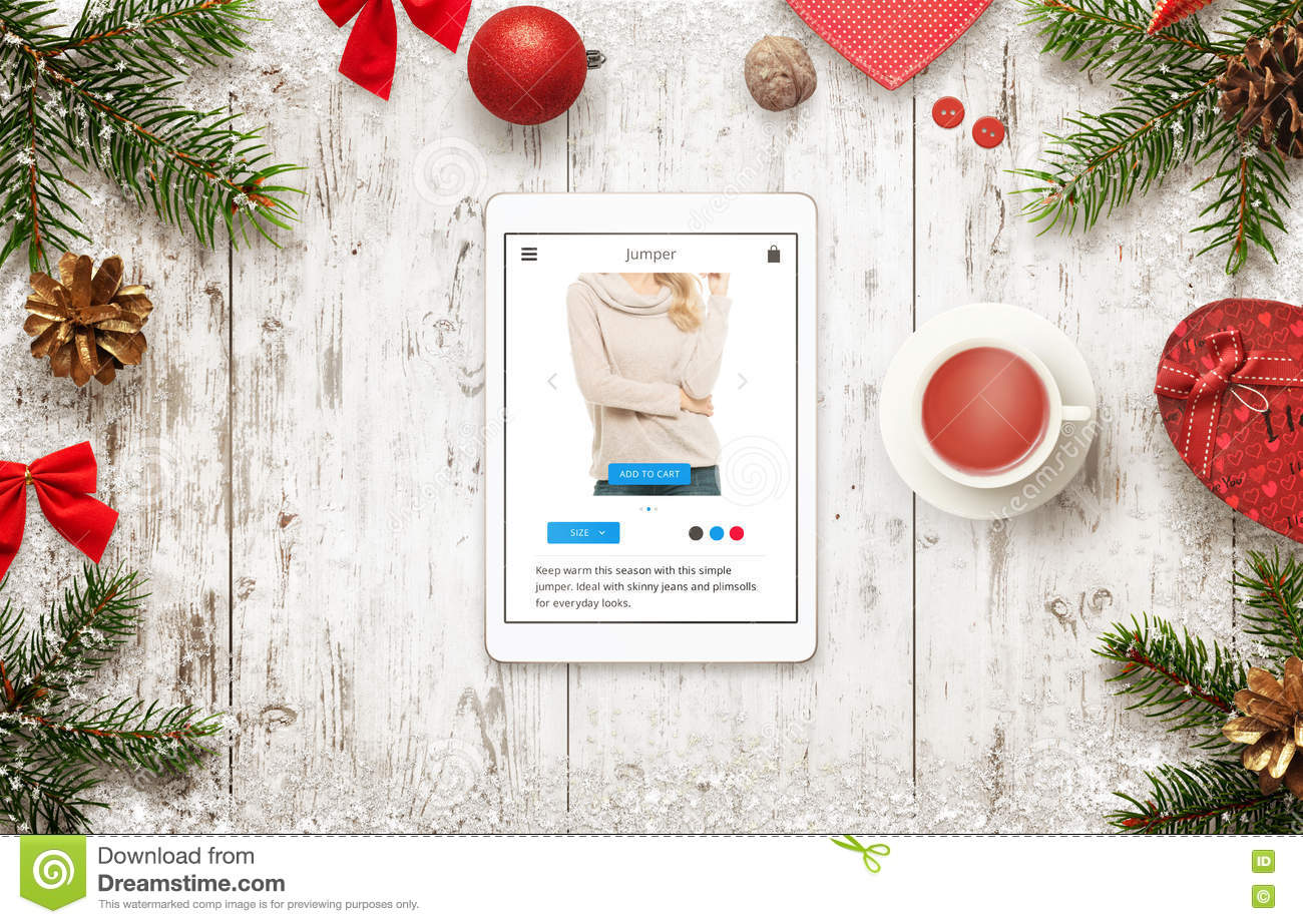 online shopping with tablet in christmas sale time top view of table with christmas decorations buying jumper on commerce website