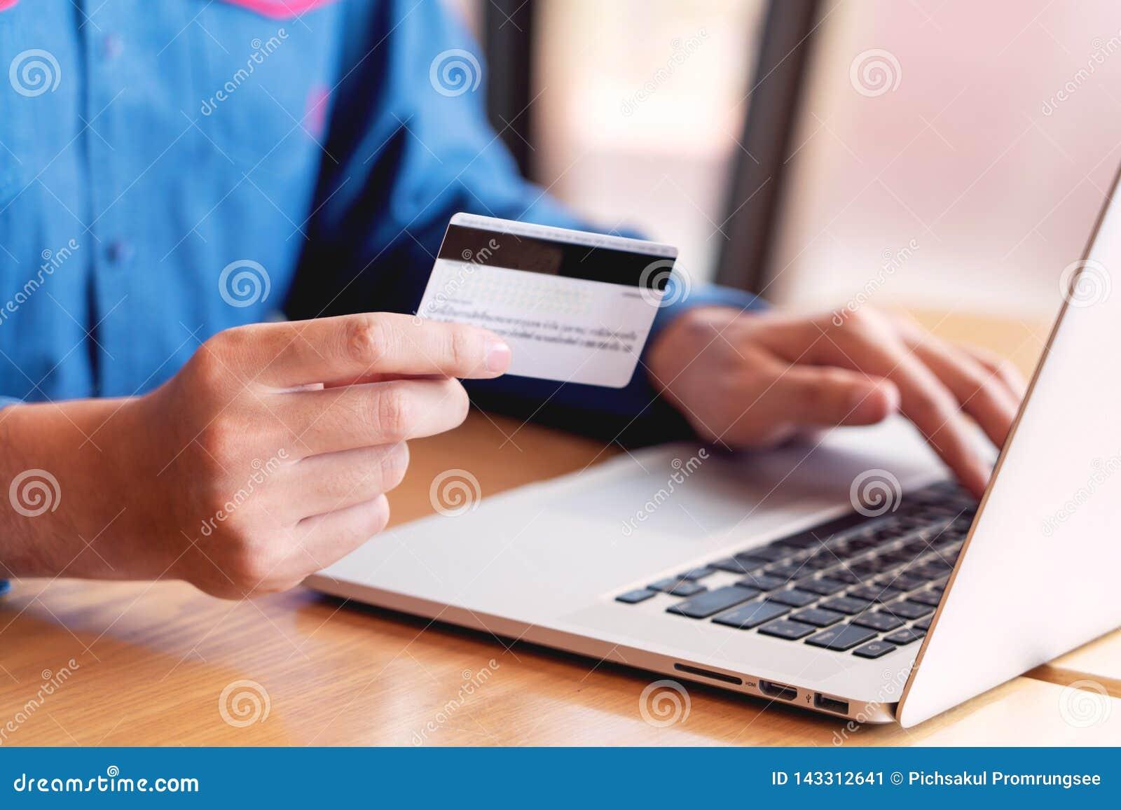 Online zakupy karty kredytowej bezpieczeństwo danych pojęcie, ręki trzyma kartę kredytową i używa mądrze laptop, telefon lub robi