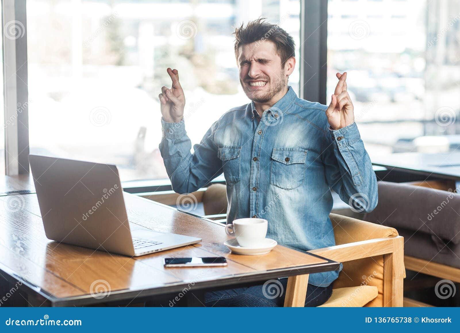 Ono modli się! Bocznego widoku portret wishful brodaty młody freelancer w niebiescy dżinsy koszula siedzi w kawiarni i działaniu