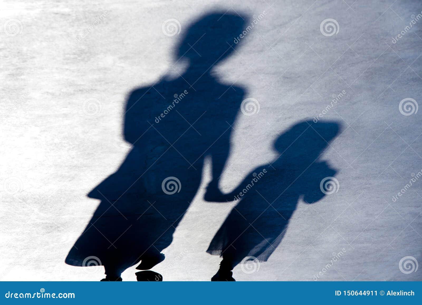 Onscherpe uitstekende schaduwensilhouetten van het tweepersoons lopen in de nacht