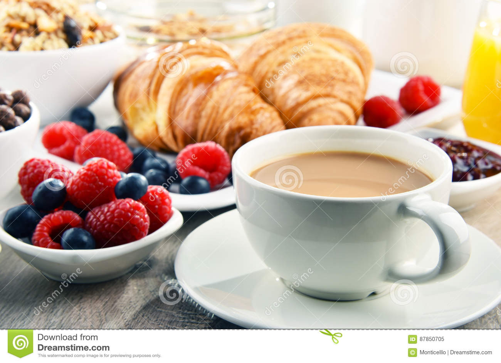 Ontbijt met koffie, sap, croissants en vruchten wordt gediend die