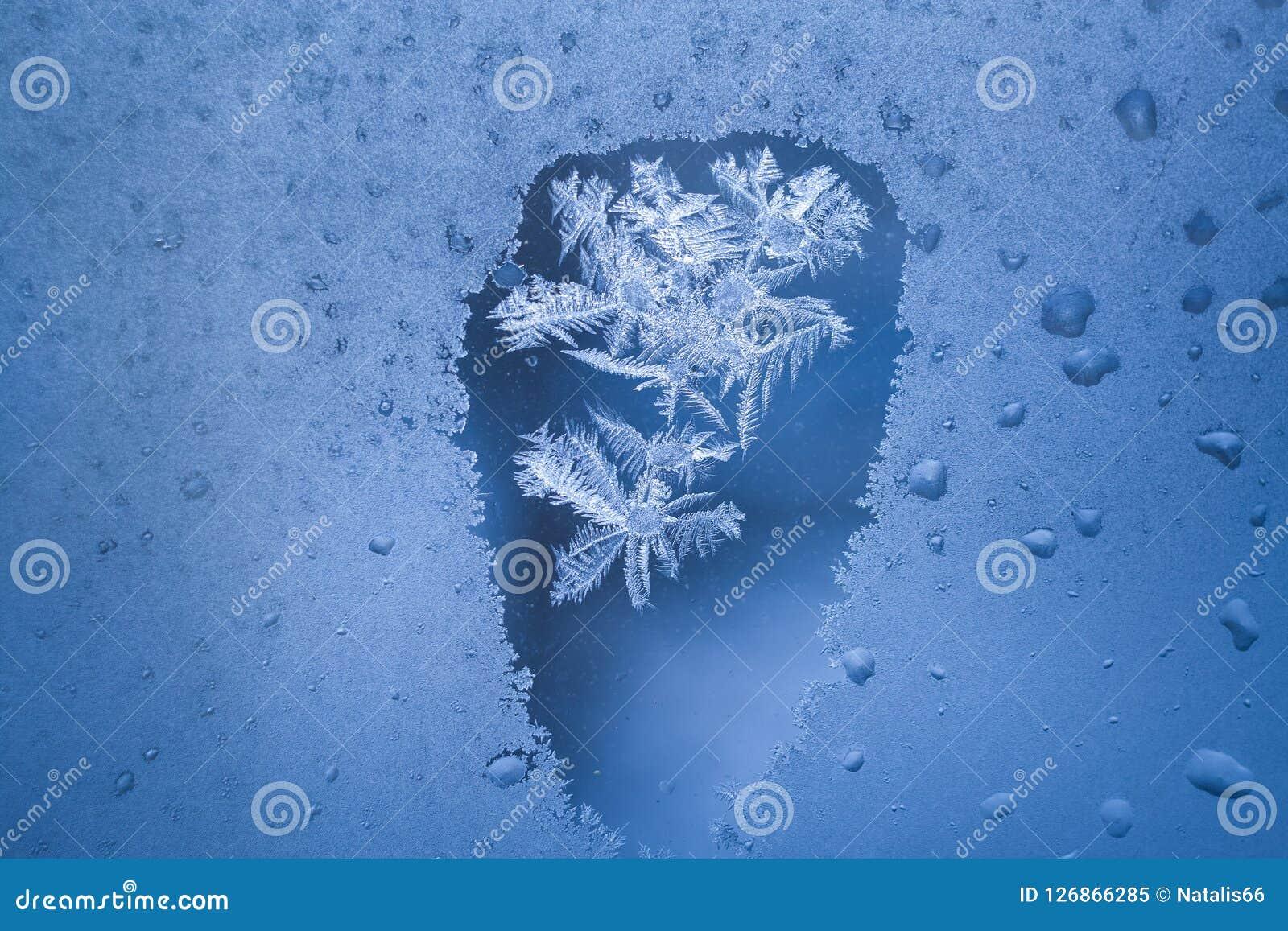 Ontdooide vlek op bevroren de wintervenster met ijzig patroon binnen het