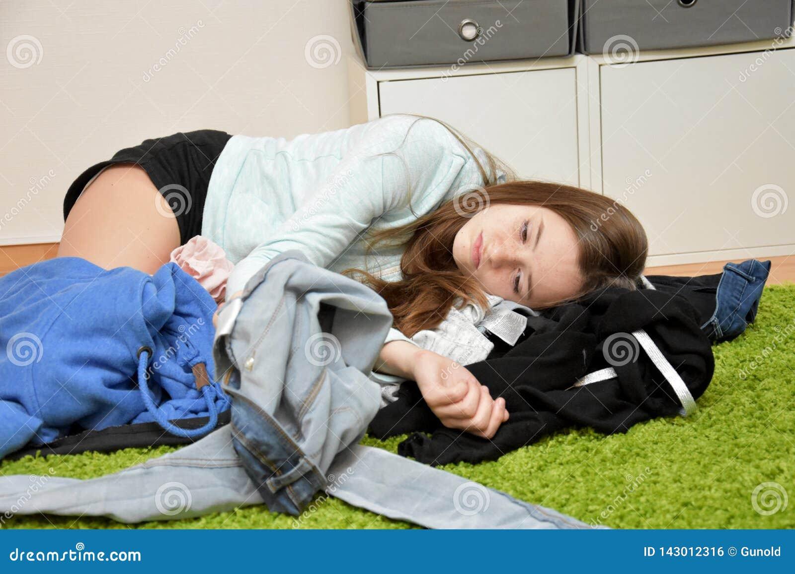 Ontevreden tiener die op de vloer in de chaos van haar uitrusting liggen