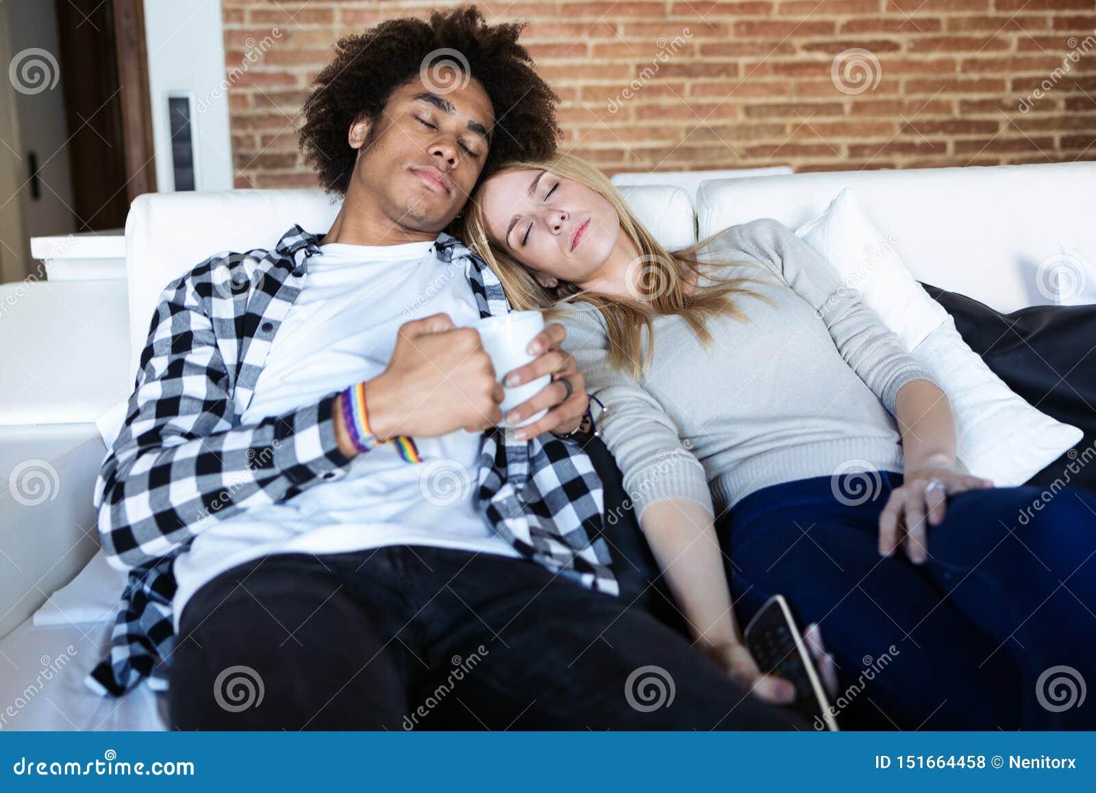 Ontspannen jong paar dat terwijl thuis het letten van op TV op de laag in slaap is gevallen