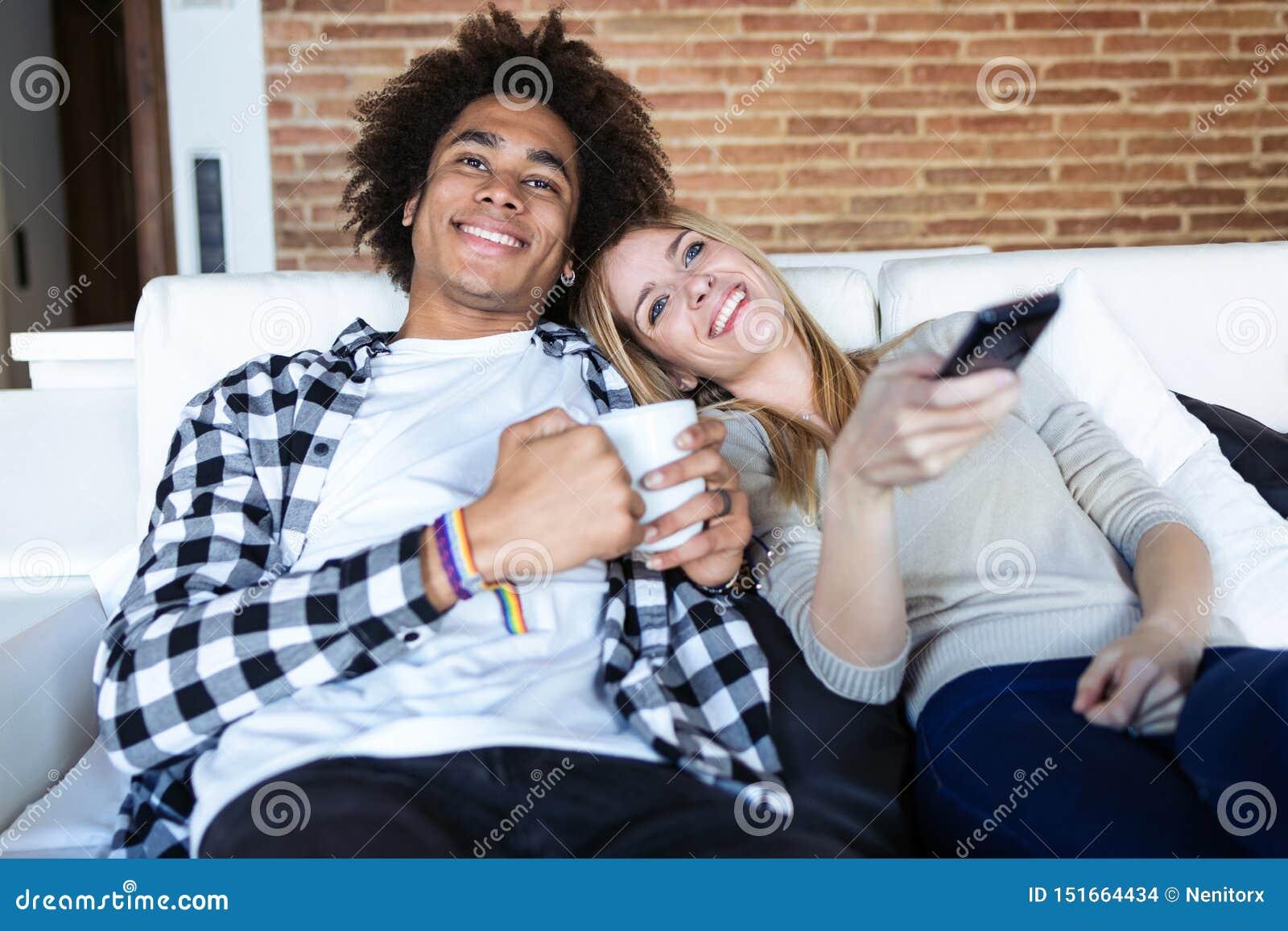 Ontspannen jonge paar veranderende kanalen met de afstandsbediening terwijl thuis het letten van op TV op de bank