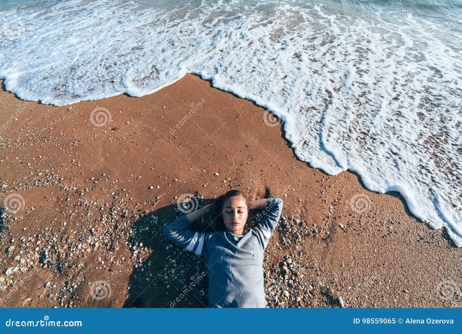 Ontspannend op zand door de overzeese golf, het concept van het dalingsstrand