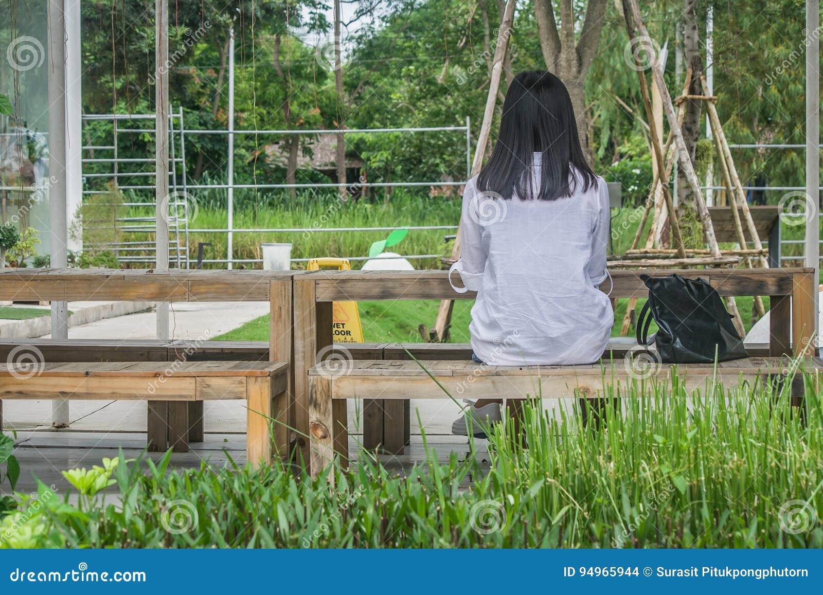 Ontspanningsconcept: De achterzitting van de meningsvrouw ontspant op houten stoel bij openluchttuin