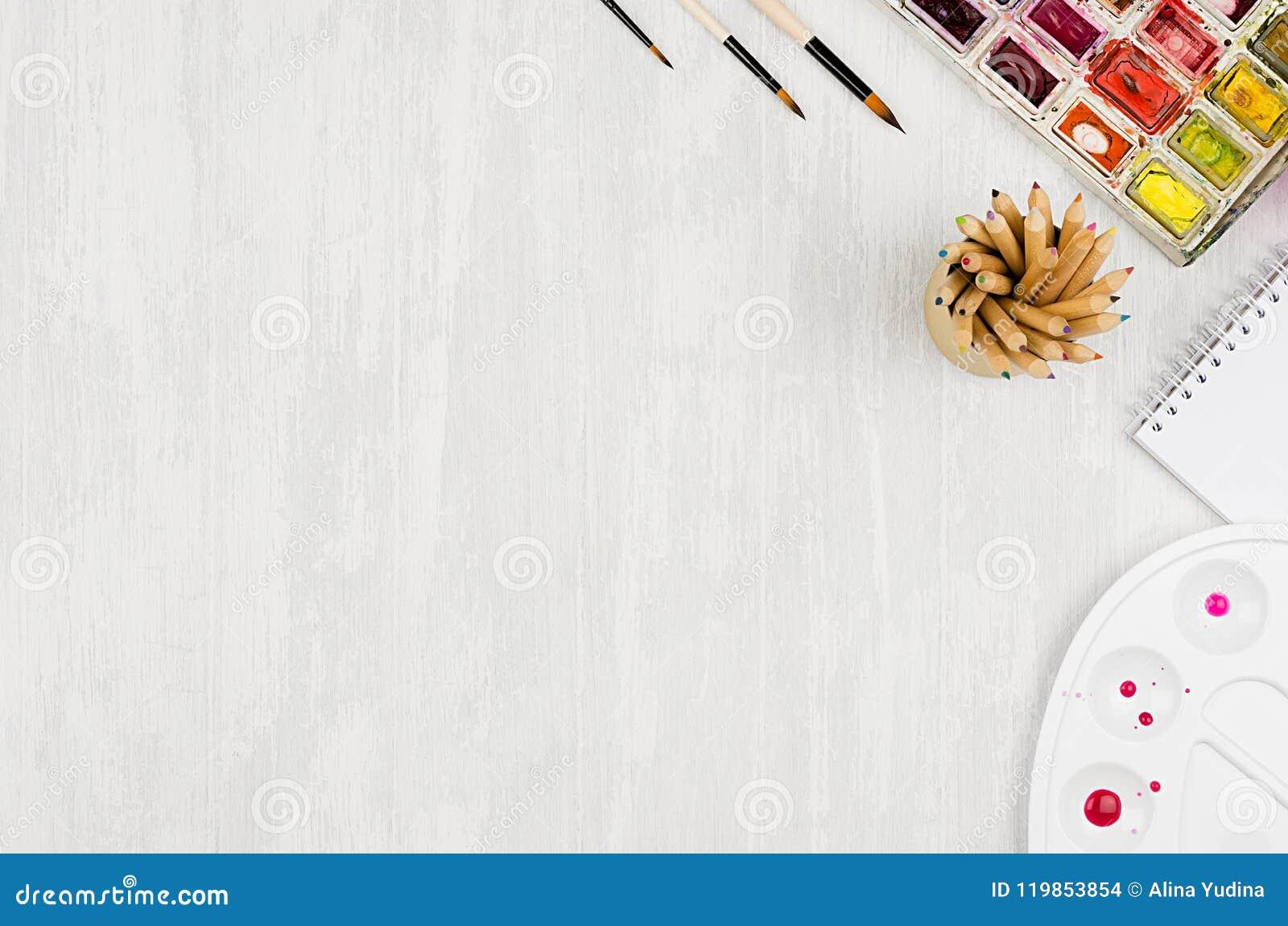 Ontwerperswerkplaats - kantoorbehoeften voor creativiteit - waterverfverven, palet, borstels, kleurpotloden op witte houten lijst