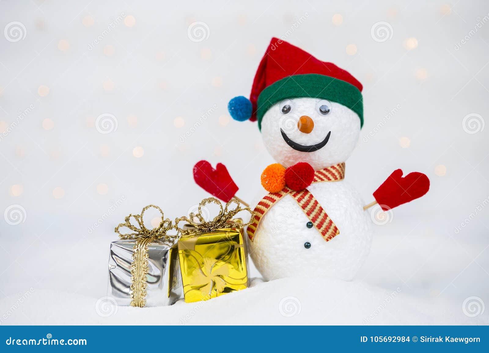 Ontwerpsneeuwman met glanzende giftdoos en denneappel op witte sneeuw