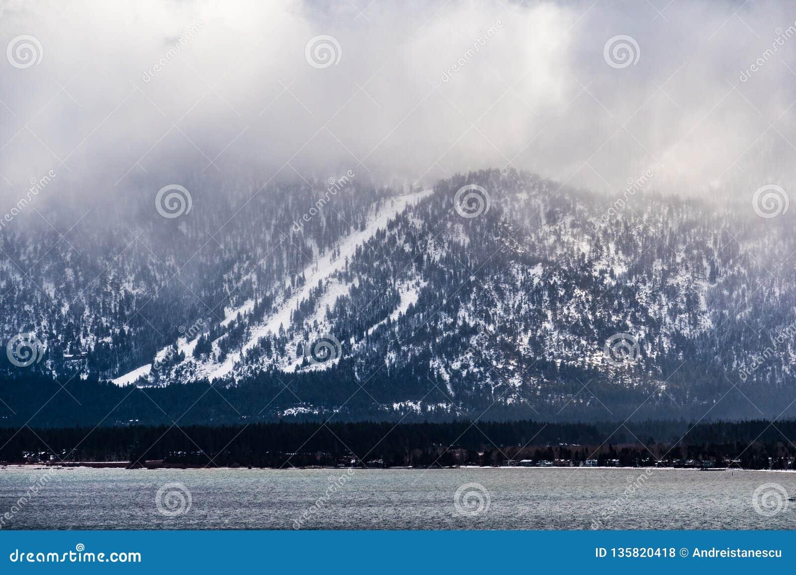 Onweerswolken die de Siërra bergen, de oever behandelen van Meer Tahoe zichtbaar in de voorgrond