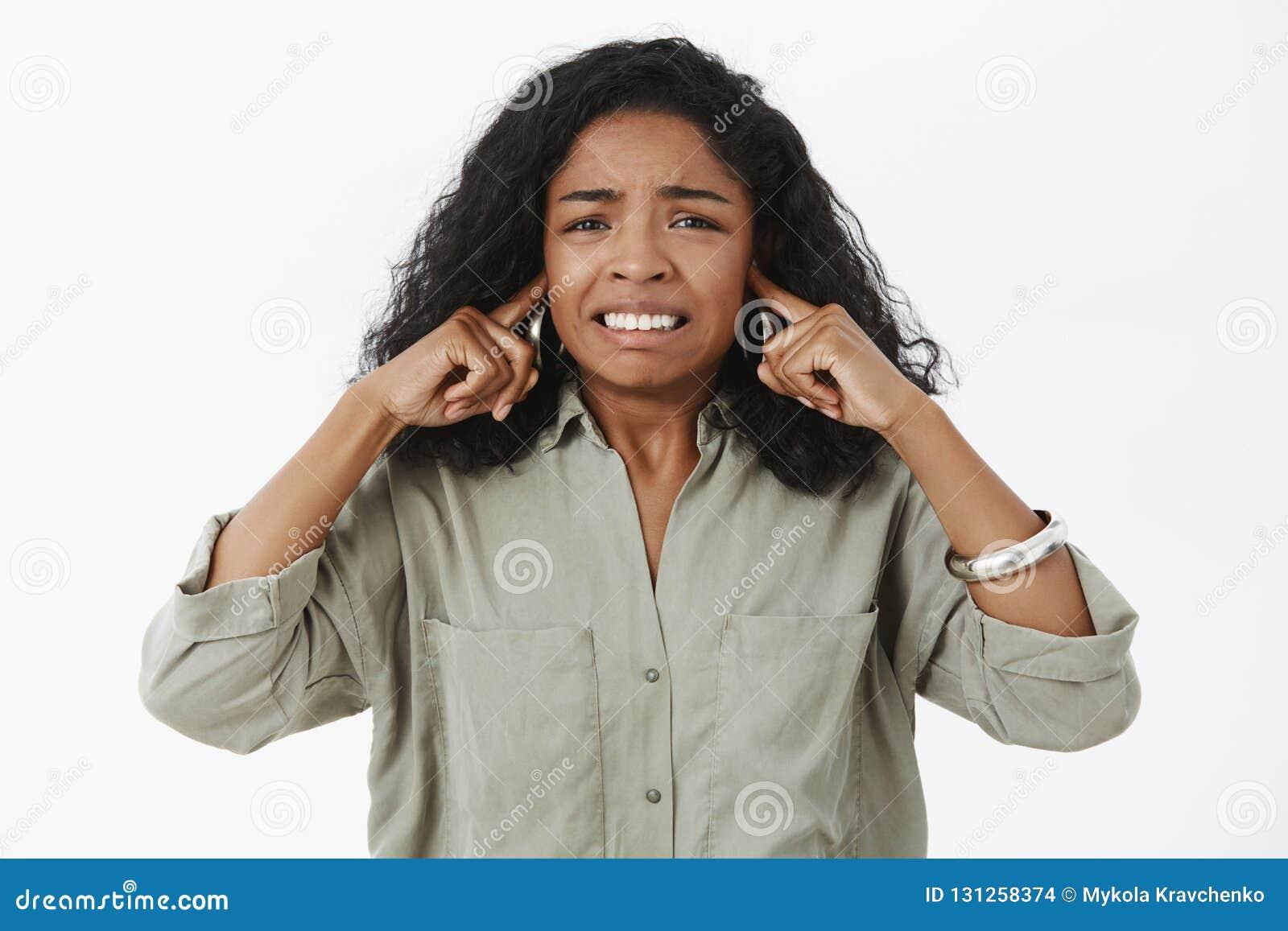 Onzekere geïrriteerde, ontstemde Afrikaanse Amerikaanse vrouwelijke student die in in overhemd tanden dichtklemmen die oren met i