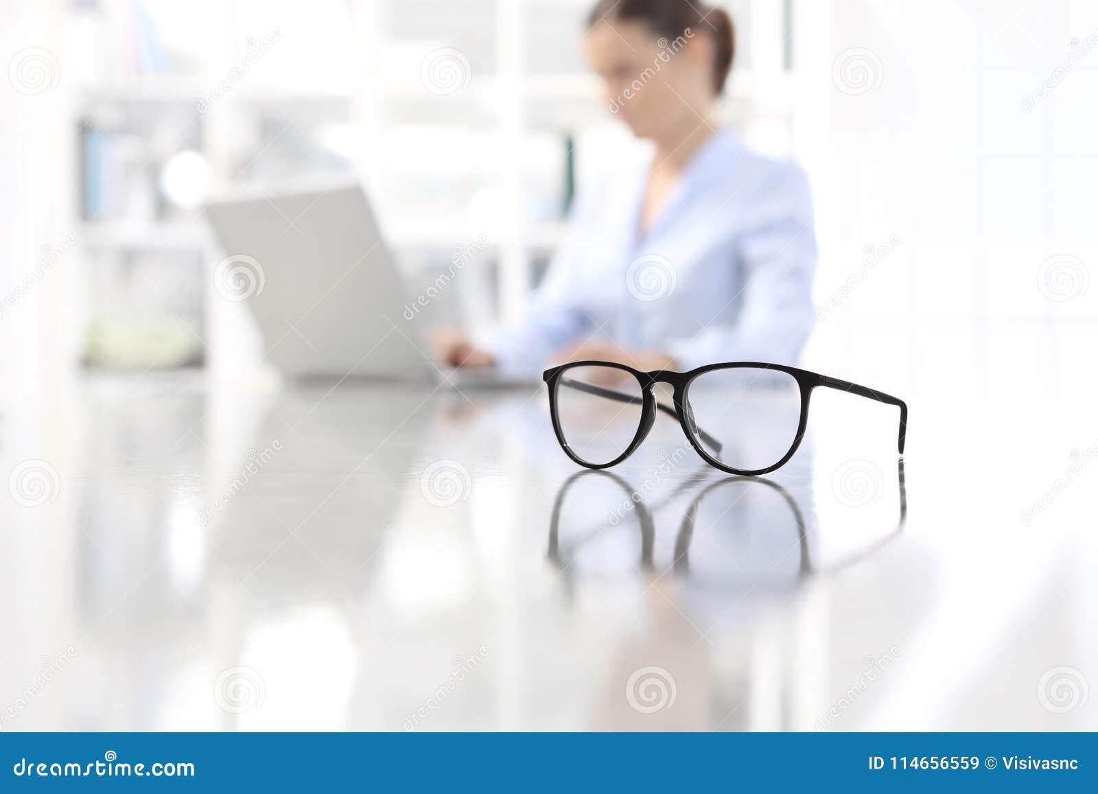 Oogglazen die op bureau en vrouw leunen die aan computer bij offi werken