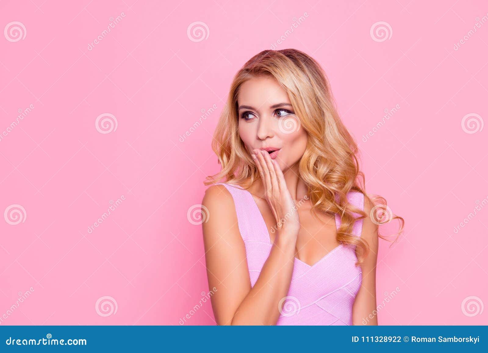 Oops! Sluit omhoog portret van sexy, mooi, geïmponeerd, verbaasd blondemeisje die haar hand houden dichtbij mond, kijkend aan de