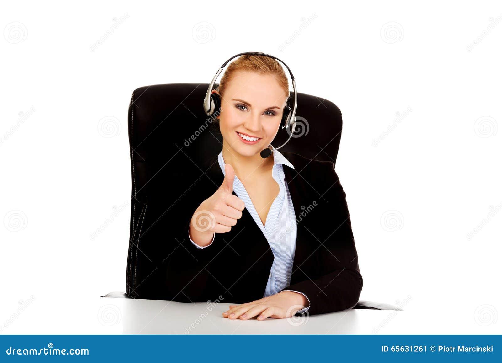 Opérateur de sourire de téléphone dans des écouteurs se reposant derrière le bureau
