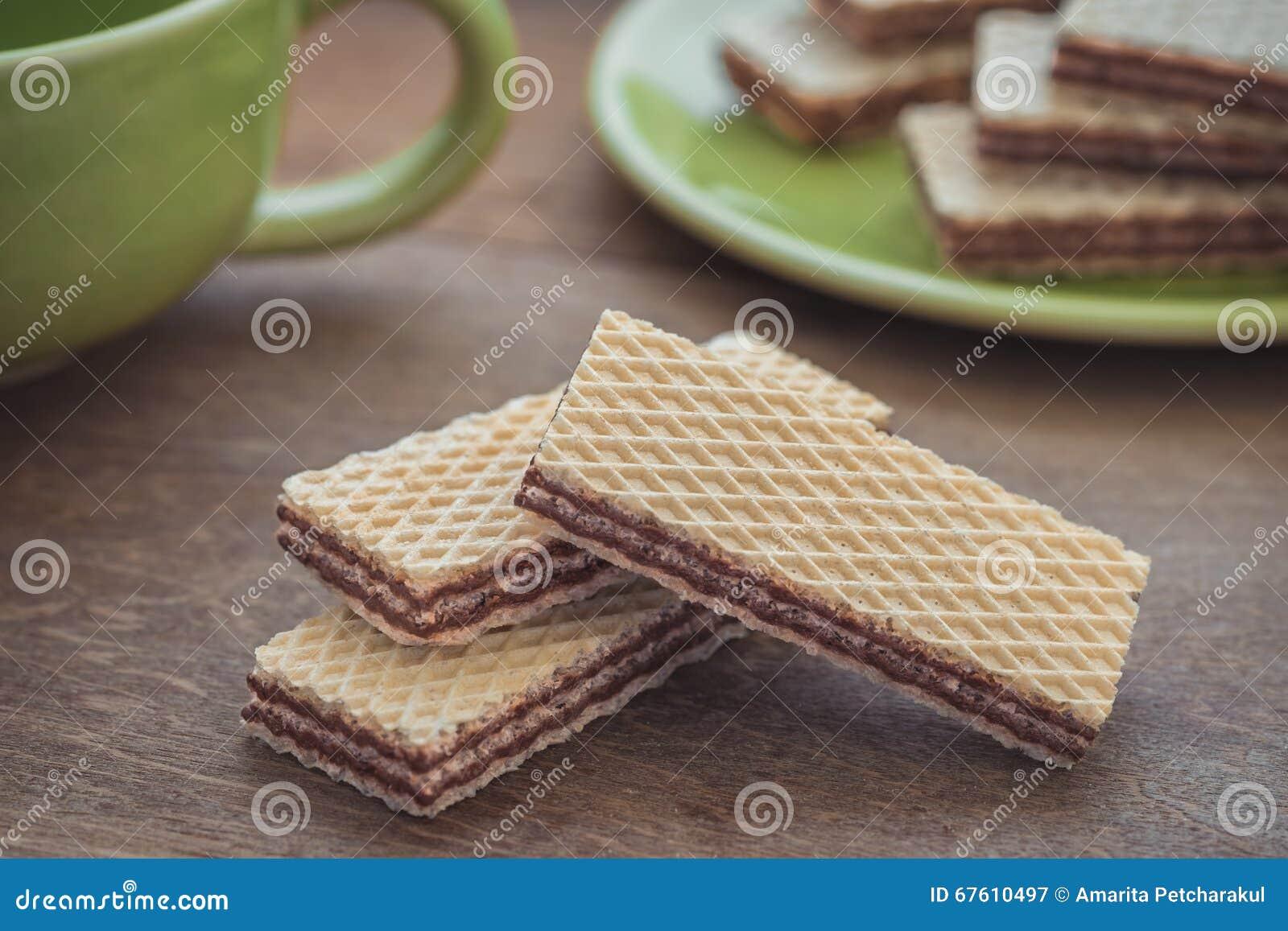 Opłatki z czekoladą na drewnianym stole i filiżance