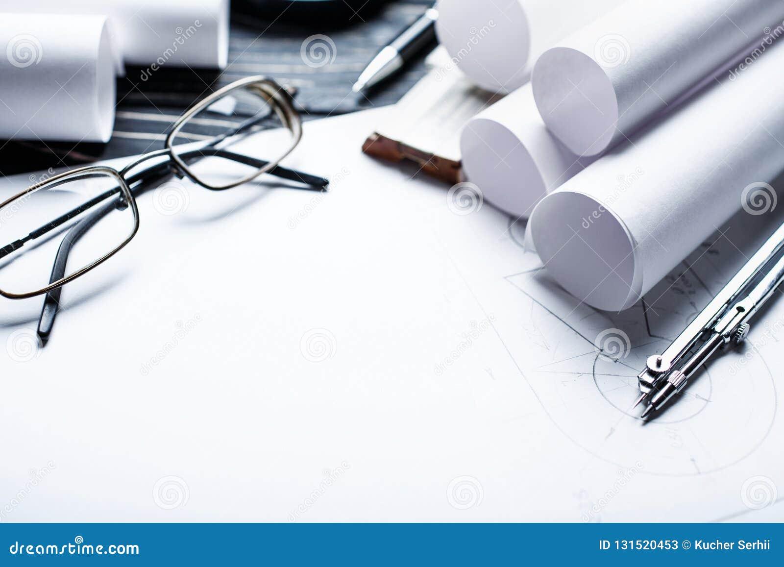 Op de houten lijst zijn er tekeningen, kompassen, potlood, heerser en glazen