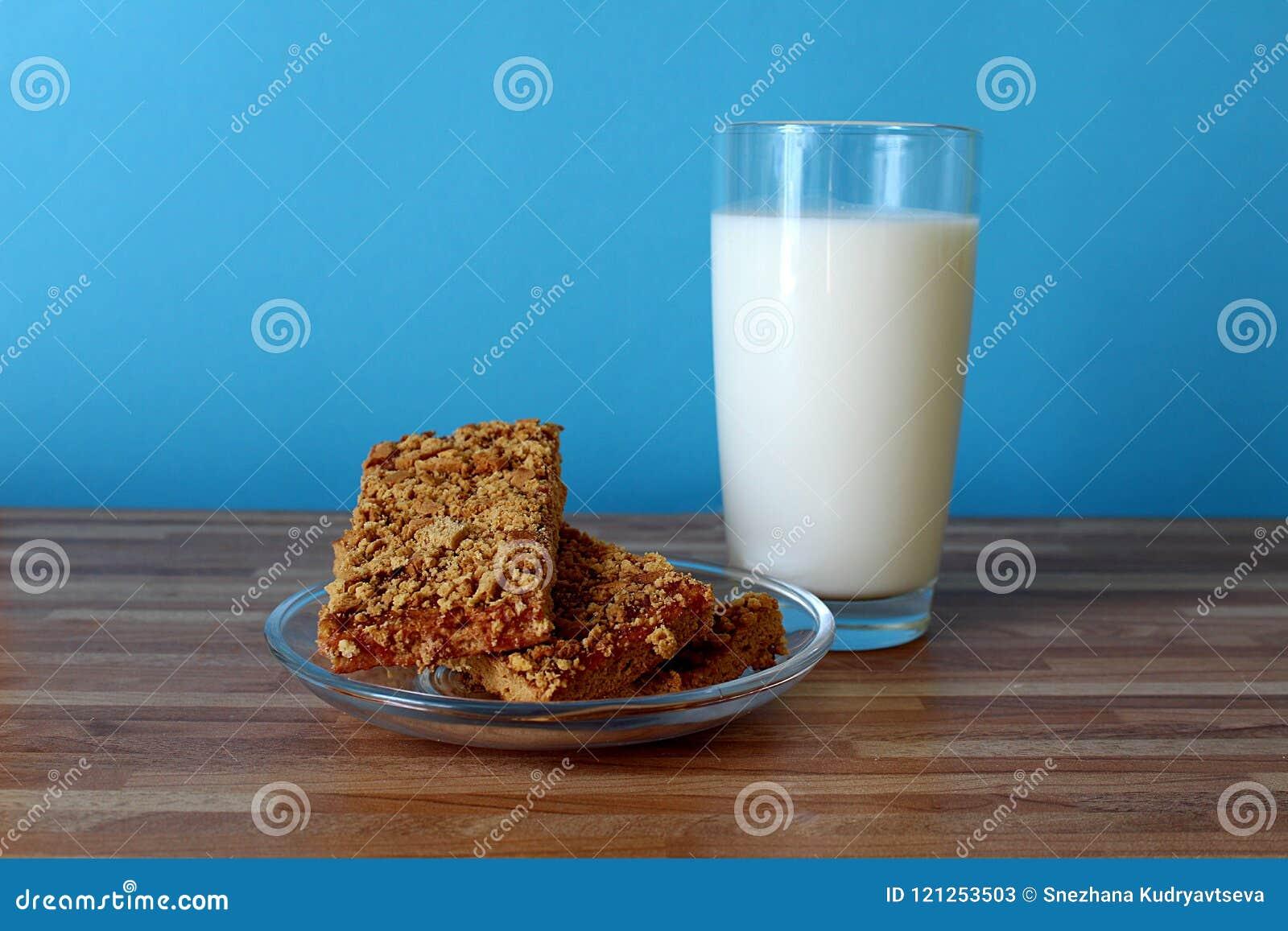 Op de lijst is een glas melk met koekjes