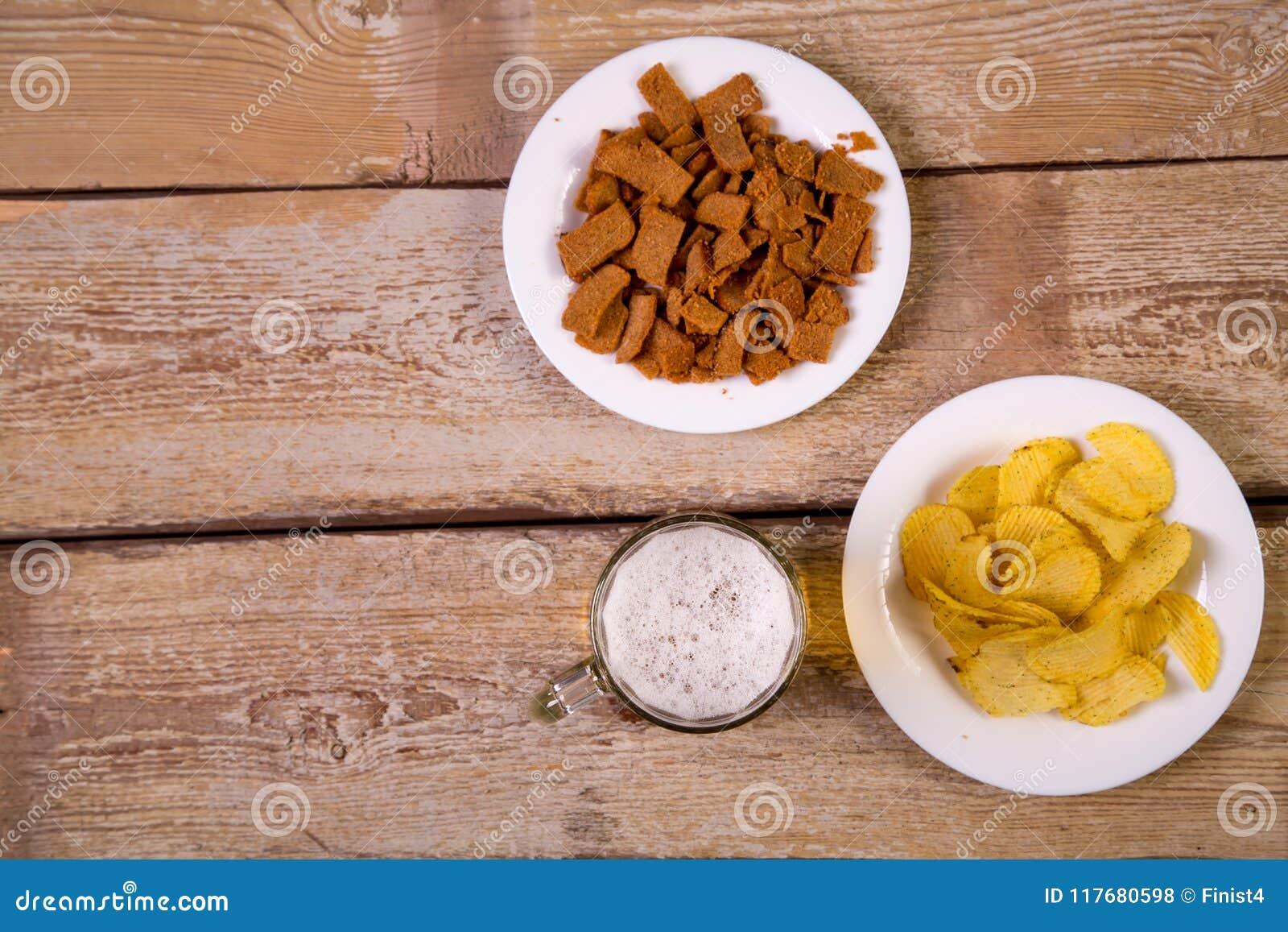 Op een houten lijst zijn witte platen met knapperige croutons en chips