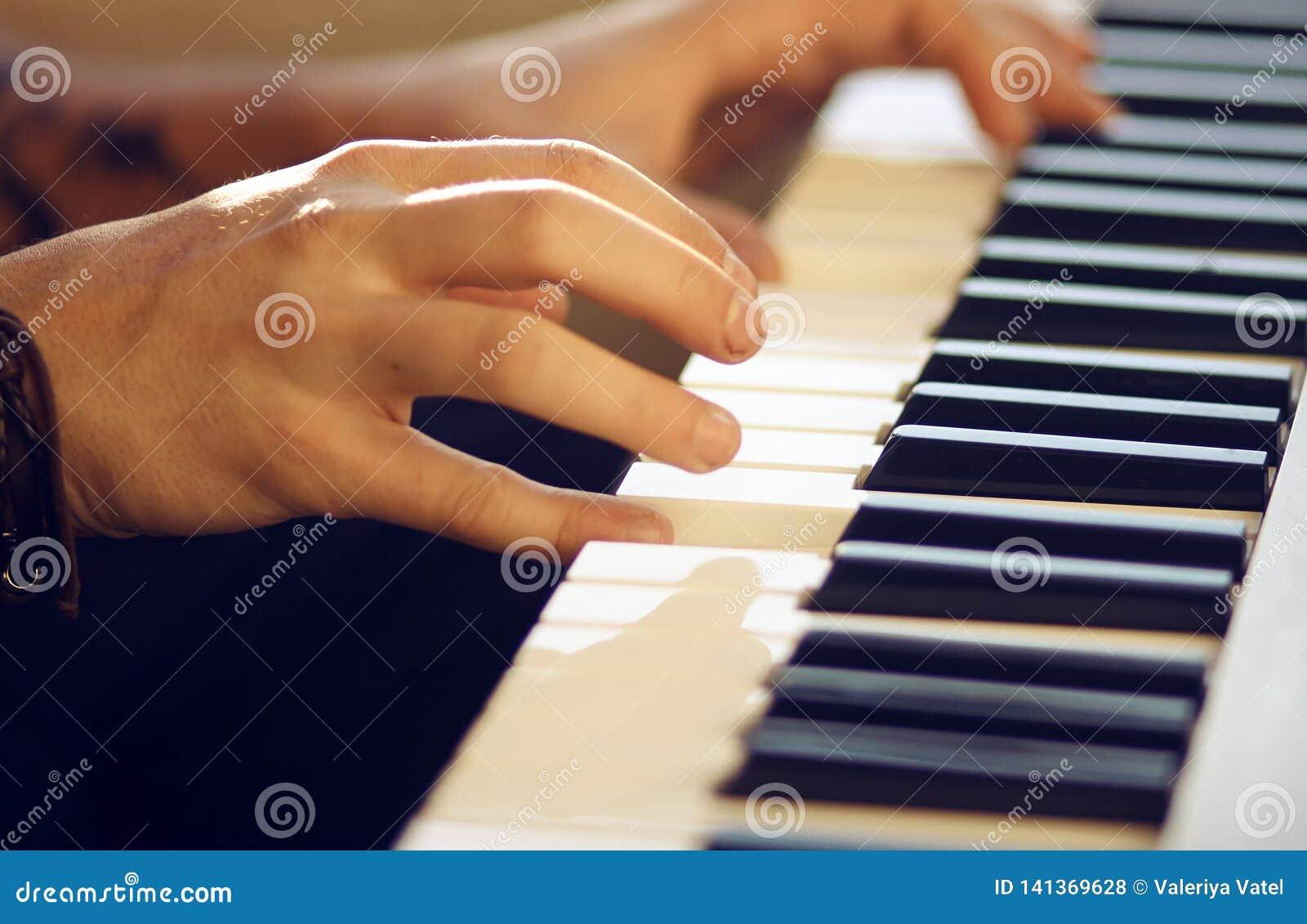 Op een muzikale mensenspelen van het toetsenbordinstrument een melodie met zijn handen